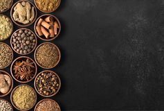 Spices over black table background. Top view of seasoning with royalty free stock photo