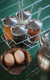 Seasoning and egg in wooden cup Royalty Free Stock Photography