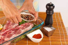 Seasoning with pepper. Seasoning raw meat with whole fresh pepper grains Stock Photography