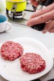 Seasoning raw burger. Hands seasoning raw burger on wooden board Stock Images