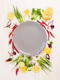 Seasoning and spices around empty gray plateon white wooden background, top view,. Copy space Stock Image