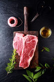 Seasoning a t-bone steak for cooking Royalty Free Stock Photo