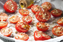 Seasoning tomatoes in a baking tray Stock Photos