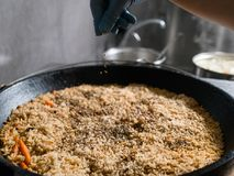 Seasoning traditional pilaf meal recipe cooking. Chef cooking and seasoning traditional Uzbek meal of pilaf. Rice and meat dish recipe Royalty Free Stock Photography