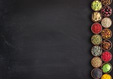 Seasonings in cups on a black table with space for food Royalty Free Stock Photography