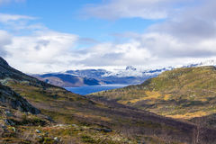 The seasons are changing. It's almost winter now with the snow having reached the highest mountain while the lower mountains still stand green and yellow stock photos