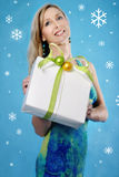 Seasons Greetings. Smiling woman holding a parcel on a blue winter background Stock Image