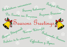 Seasons Greetings - Banner card - Multi Languages. Snowflake background with festive bells surrounded by seasons greetings in multiple languages Stock Images