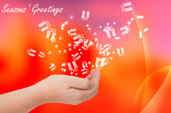 Seasons greetings card. With hand open on red background Stock Image