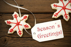 Seasons Greetings with Christmas Star Cookies. Red and white Christmas Star Cookies with Label on which stands Seasons Greetings Stock Photography