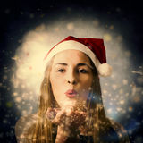 Seasons greetings girl. Fine art Christmas portrait of a lovely young blond woman blowing magic snow dust in an expression of xmas love. Seasons greetings Royalty Free Stock Photography