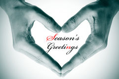 Seasons greetings. Man hands forming a heart and the sentence seasons greetings Royalty Free Stock Images