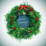 Seasons greetings. A natural christmas wreath with pine cones, berries and a red ribbon bow and a chalkboard with the text seasons greetings written in it Stock Images