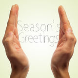 Seasons greetings. Picture of man hands and text seasons greetings in a beige background with a retro effect Royalty Free Stock Image