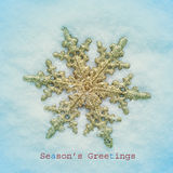 Seasons greetings. Picture of a snowflake-shaped christmas ornament and the text seasons greetings on the snow with a retro effect Royalty Free Stock Photos