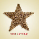 Seasons greetings. A rustic christmas star and the text seasons greetings on a beige background Stock Images