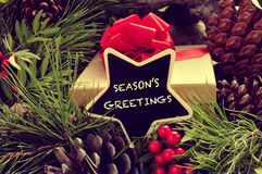 Seasons greetings. A star-shaped signboard with the text seasons greetings written in it, with a gift and some natural ornaments such pine cones and red berries Royalty Free Stock Image