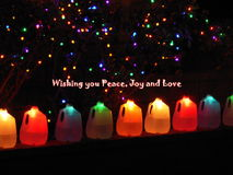 Seasons greetings. Text 'Wishing you Peace, Joy and Love' with a row of colorful bottles and background of 'stars' in an otherwise dark sky Royalty Free Stock Photo