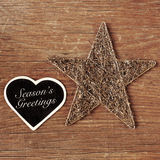 Seasons greetings written in a heart-shaped chalkboard. The sentence seasons greetings written in a heart-shaped chalkboard and a rustic christmas star on a Stock Photos