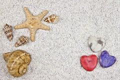 Seastar and shells. A seastar and several shells in white sand with three hearts Royalty Free Stock Photo
