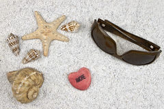 Seastar and shells. A seastar and several shells in white sand with sunglasses and a heart Royalty Free Stock Photography