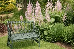 Seat Amongst the Flowers. Garden Seat in an English Garden Royalty Free Stock Images