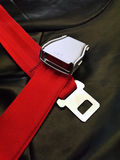 Seat belt. Red seat belt with black background shot in airplane Royalty Free Stock Photos