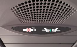 Seat belt and Smoking sign on a plane stock image