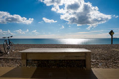 Seat, bench, beach, bycicle. Wooden bench and bycicle on beach on a sunny day, sea and sky Royalty Free Stock Photos