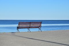 Seat bench on paved bank of river. Seat bench on stone paved riverbank or sea resort over background of blue water and clear sky, sunny day, rear view Stock Photo