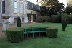 Seat byggde in i häckarbete och tappningurnan på en sockel i en trädgård arkivbilder