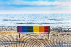 Seat in front of the beach painted with the colors of the LGBT flag. LGBT icon bench in front of the beach painted with the colors of the LGBT flag stock photo