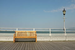 Seat and light. A wooden seat on a boardwalk against a silver painted railing with a light on a post against the sea and sky Royalty Free Stock Photography