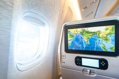 Seat-monitor dichtbij venster in passagiersvliegtuig. Stock Afbeelding