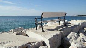 Seat på havet Den vita bänken vaggar på på stranden av havet Den härliga sikten av bänkvit vaggar och stenar med det blåa Adriati lager videofilmer