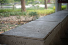 Seat in the park. Long cement seat in the park royalty free stock photography