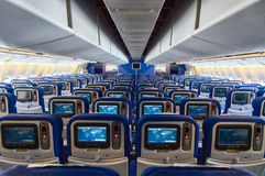 Seat rows with video screens inside an airplane Stock Images