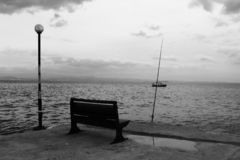 Seat by the sea. Street lamp and fishing rod. stock photo