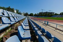 Seat in the stadium province running track and grass green field. Bright sunny day blue clear sky blue seating in the stadium grass green field and track running Stock Photography