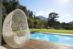 Seat suspendido al lado del Decking alrededor de la piscina al aire libre foto de archivo libre de regalías
