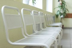 Seat waiting for the doctor in the hospital.Empty and clean waiting area with metallic chairs in clinic. in an corridor. Seat waiting for the doctor in the royalty free stock photo