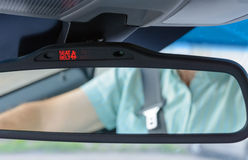 Seatbelt sign showing on the Car Rearview Mirror Royalty Free Stock Photos