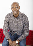 Seated African American man. Man in a check shirt sitting on a red quilted seat Stock Image
