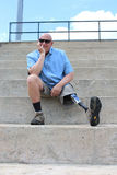 Seated amputee man with prosthetic leg outstretched. Man with prosthesis seated on concrete bleachers stock image