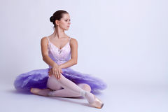 Seated ballerina. Picture of a seated ballerina wearing a purple tutu Stock Image