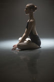 Seated ballerina in class room. Pacified ballerina sitting in the lotus position on the floor in the dark dance hall. She is wearing the black leotard with Royalty Free Stock Photography