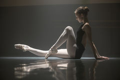 Seated ballerina in class room. Pretty ballerina sitting on the floor in the dance hall. She leans her hands on the floor from the back while pulling one leg stock photo