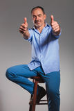Seated bearded man in jeans showing thumbs up Royalty Free Stock Photo