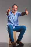 Seated bearded mature man in jeans, showing thumbs up Stock Photos