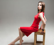 Seated beautiful woman in a red dress on white background Royalty Free Stock Image